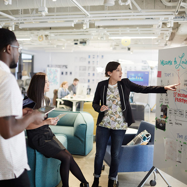 Woman pointing to a whiteboard while two people watch.