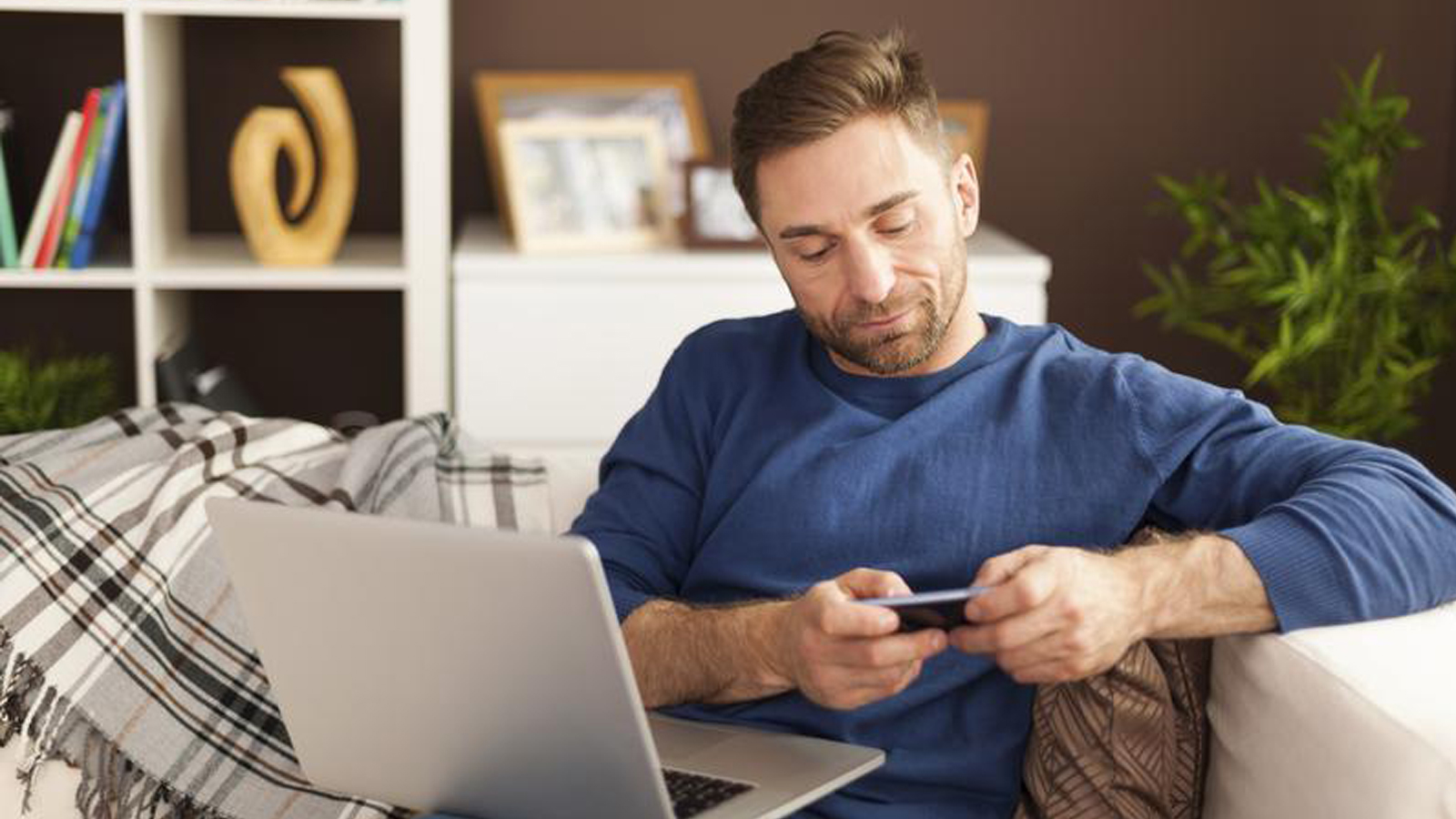 A man sitting on a sofa looking at his mobile phone with a laptop open in front of him.