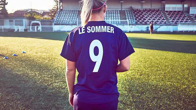 Eugenie Le Sommer wearing her jersey with the number nine on it facing the football pitch with her back faced towards the camera.