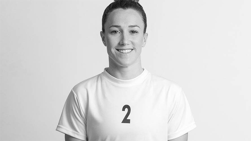 Lucy Bronze smiling at the camera wearing her jersey with the number two on it.